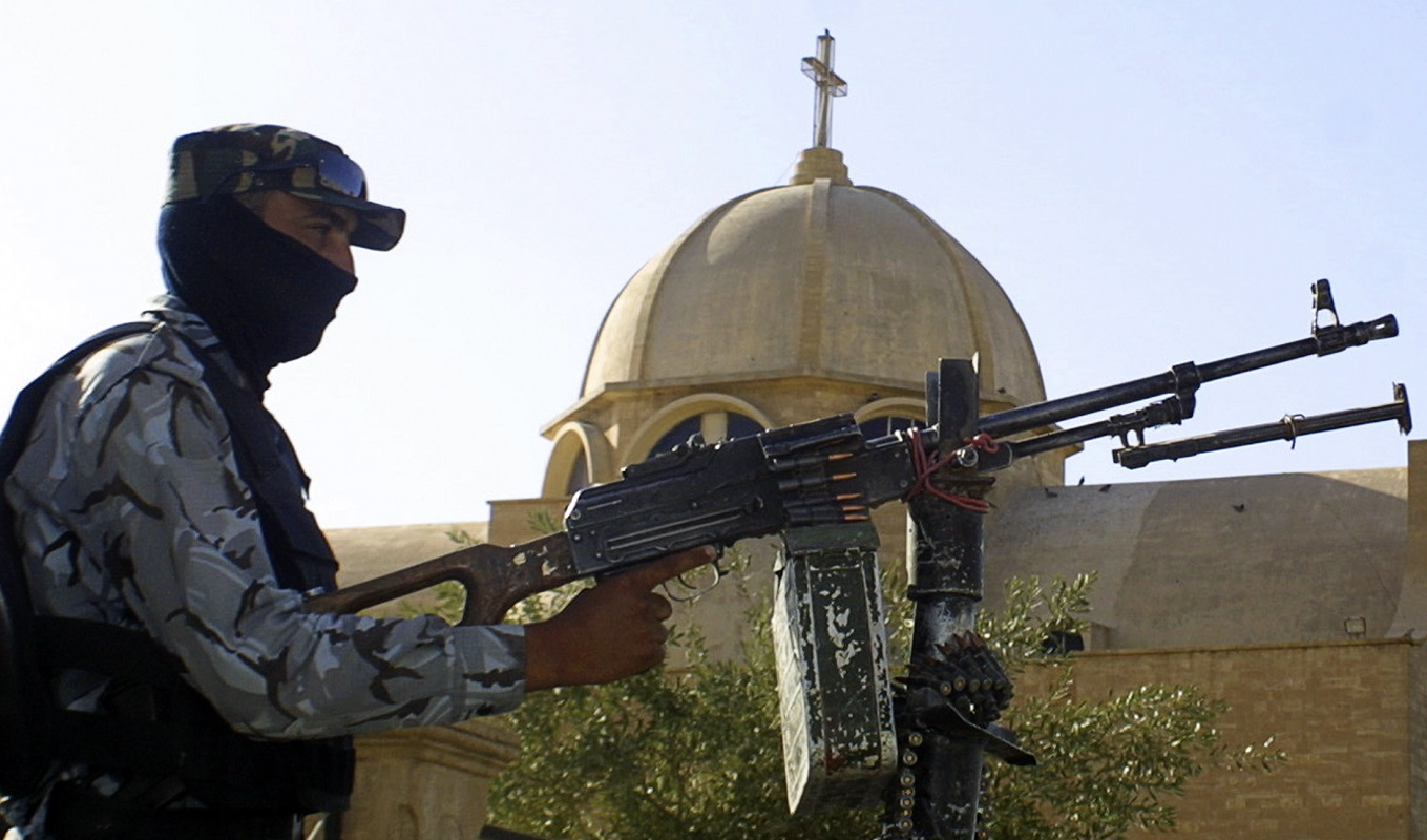 A masked policeman mans a machinegun atop an armoured vehicle to secure a Christian church in Mosul